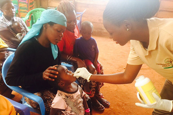 A picture of an UnbridledACTS Africa representative providing oral care for a small child.
