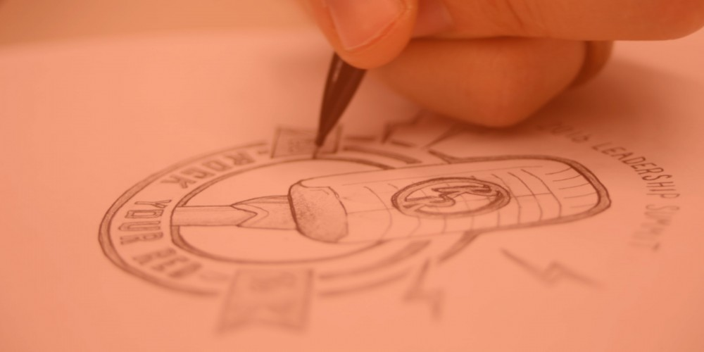 Hand drawing a logo on paper