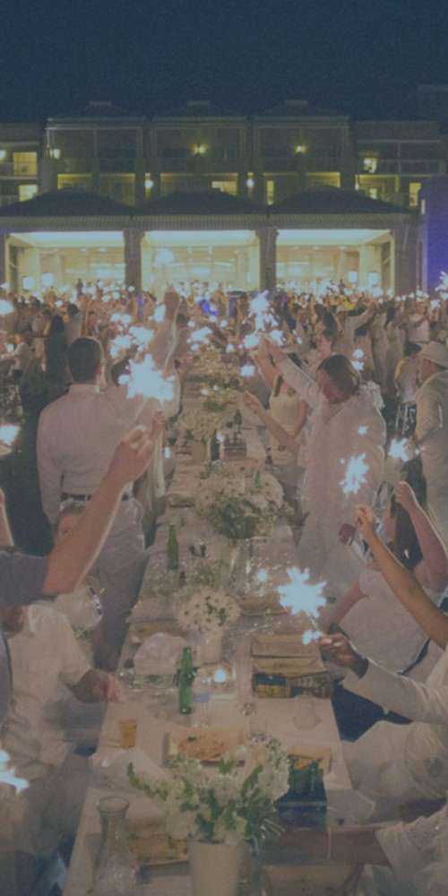People all in white, sitting at tables holding up sparklers